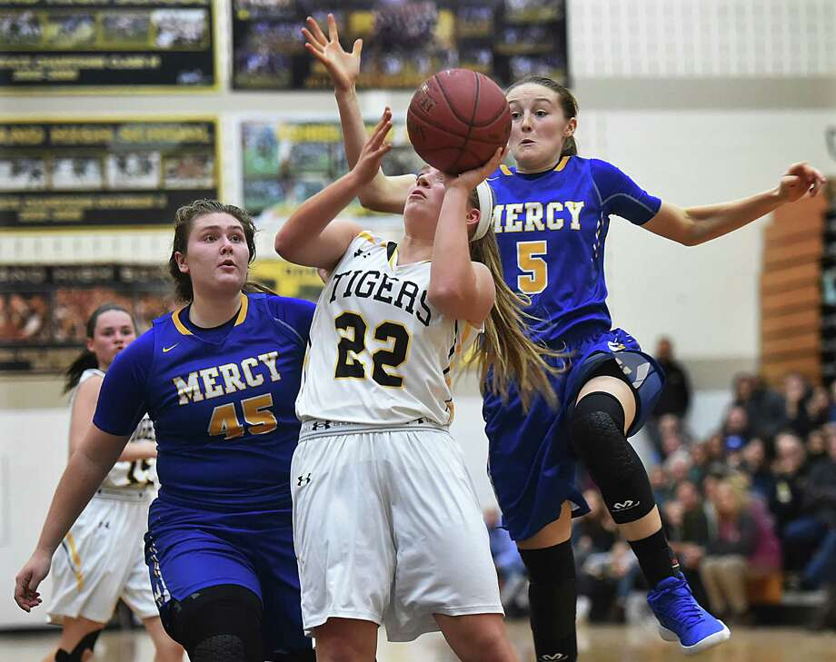 Hand's Gabby Egidio elevates to the hoop as Mercy's Meg Deville and Bella Santoro defend, Thursday, Dec. 14, 2017, at Daniel Hand High School in Madison. Mercy won, 50-40. Photo: Catherine Avalone, Hearst Connecticut Media / New Haven Register