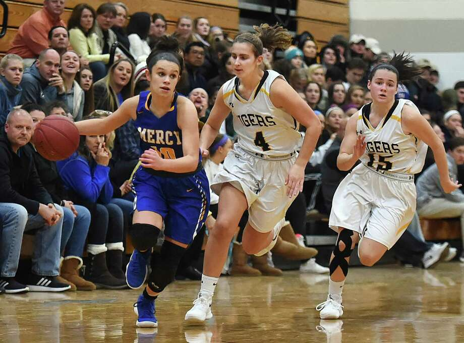 Mercy's Lexi Leon drives past Hand's Hannah Martin (4) and sophomore Sara Wohlgemuth (15) on Thursday. Photo: Catherine Avalone / Hearst Connecticut Media / New Haven Register