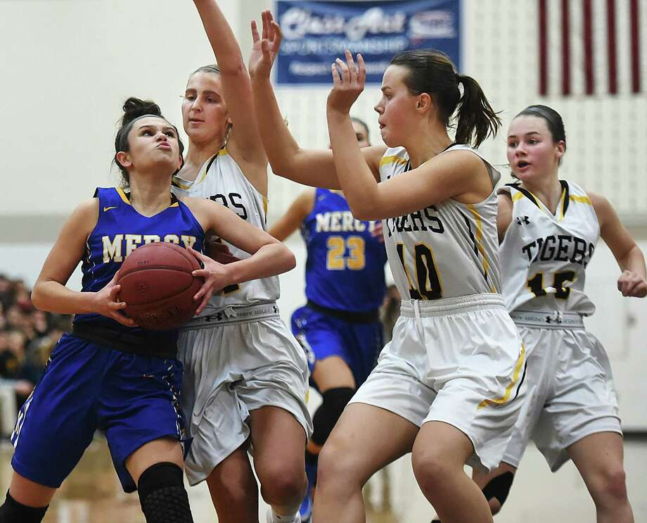 Mercy's Lexi Leon elevates to the hoop as Hand's Hannah Martin (4) and senior Halle Freund (10) defend on Thursday. Photo: Catherine Avalone / Hearst Connecticut Media / New Haven Register