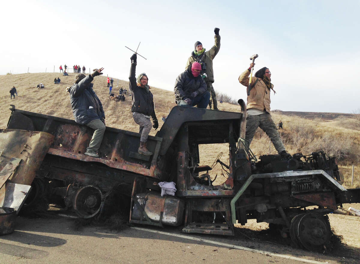 FILE - In this Nov. 21, 2016, file photo, protesters against the Dakota Access oil pipeline stand on a burned-out truck near Cannon Ball, N.D. An appeals court ruling Tuesday, Nov. 14, 2017 has cleared the way for the resumption of a lawsuit filed a year ago by opponents of the Dakota Access oil pipeline over alleged police brutality and civil rights violations, after a nine-month delay. The plaintiffs' attorney believes their case has been bolstered by developments since it was put on hold. A judge has said the protesters are unlikely to succeed. (AP Photo/James MacPherson, File)