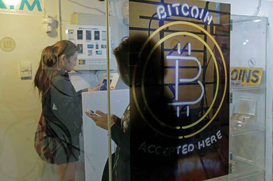 FILE - In this Friday, Dec. 8, 2017, file photo, people use a Bitcoin ATM in Hong Kong. The public's intense interest in all things bitcoin, and efforts by entrepreneurs to fund their businesses with digital currencies, has begun to draw attention from regulators. (AP Photo/Kin Cheung, File) Photo: Kin Cheung, STF / Copyright 2017 The Associated Press. All rights reserved.