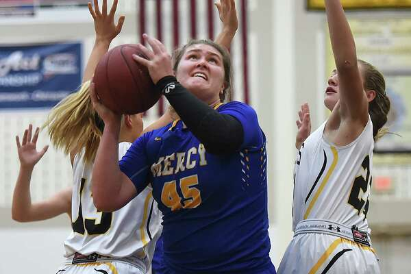 Mercy senior Meg Deville eyes the hoop as Hand junior Anna Beccia (13) and  defeats Hand, 50-40, Thursday, Dec. 14, 2017, at Daniel Hand High School in Madison.