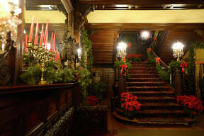 Christmas decorations and poinsettias in the entryway of the McFaddin-Ward House Museum during the egg nog open house on Thursday evening. Photo taken Thursday 12/14/17 Ryan Pelham/The Enterprise