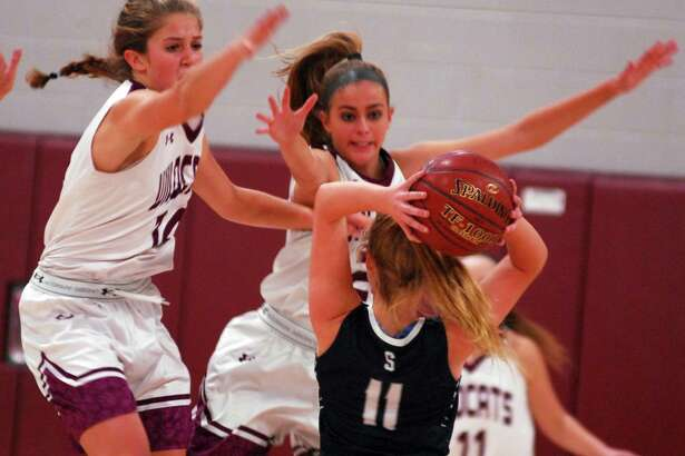 Staples' Elle Fair is defended by Bethel's Lily Daniels and Britney Roach during a game on Thursday.