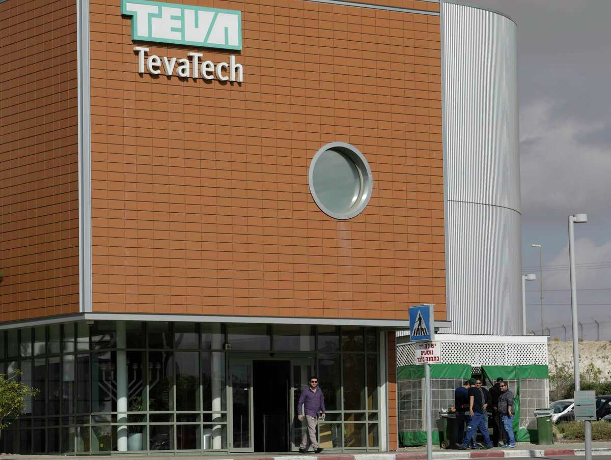 A man walks out of Teva Pharmaceutical facility building in Neot Hovav, Israel, Thursday, Dec. 14, 2017. Teva Pharmaceutical Industries Ltd., the world's largest generic drugmaker, says it is laying off 14,000 workers as part of a global restructuring. The company said Thursday that the layoffs represent over 25 percent of its global work force. (AP Photo/Tsafrir Abayov) ORG XMIT: DV102