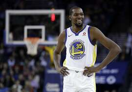 Golden State Warriors' Kevin Durant smiles during a break in play during the second half of an NBA basketball game against the Dallas Mavericks Thursday, Dec. 14, 2017, in Oakland, Calif. (AP Photo/Marcio Jose Sanchez)