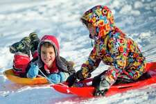 Gabriel Mendes, 4, holds on to the sled of his older brother Marcelo Mendes, 7, both of Midland, while they slide down a hill Thursday in Revere Park. (Katy Kildee/kkildee@mdn.net)