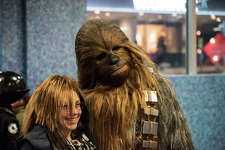 A fan dressed as Chewbacca poses with moviegoers before the public premiere of Star Wars: The Last Jedi, at Cinerama on Thursday, Dec. 14, 2017.