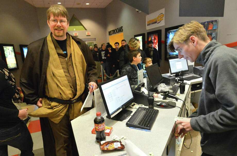 Peter Keeler of Stamford buys some snickers, starburst and a Dr. Pepper while wearing the robes of a Jedi Master during the national premiere of The Last Jedi at The Maritime Aquarium's 70mm film projection IMAX Theater on Thursday December 14, 2017 in Norwalk Conn. Photo: Alex Von Kleydorff / Hearst Connecticut Media / Norwalk Hour