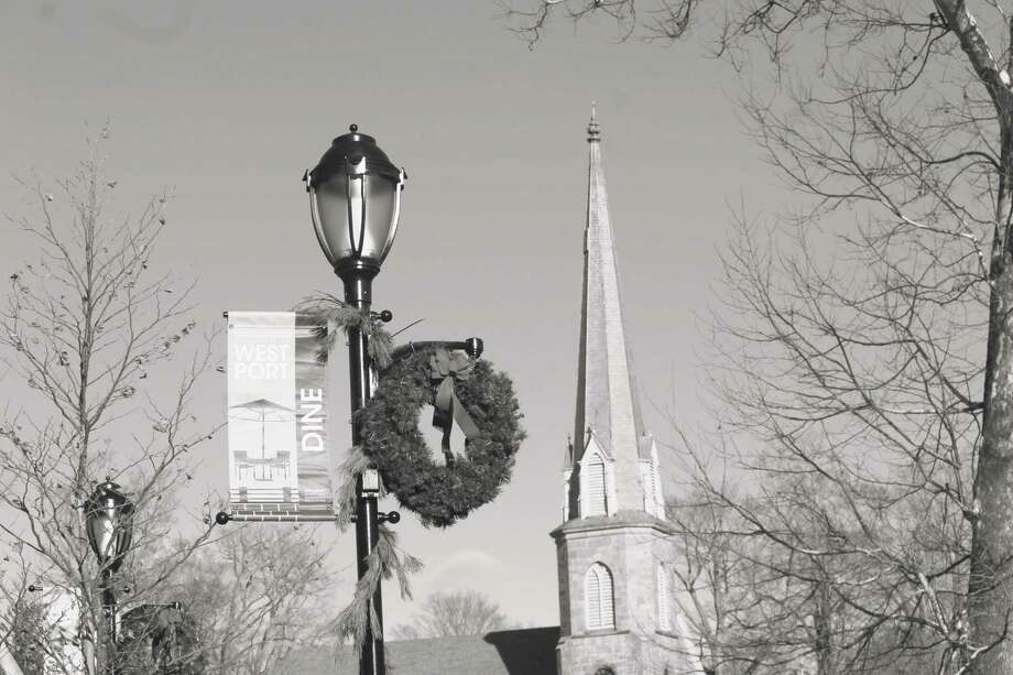 A Christmas wreath on Church Lane, with the steeple of Christ & Holy Trinity Episcopal Church behind. Photo: Justin Papp / Hearst Connecticut Media