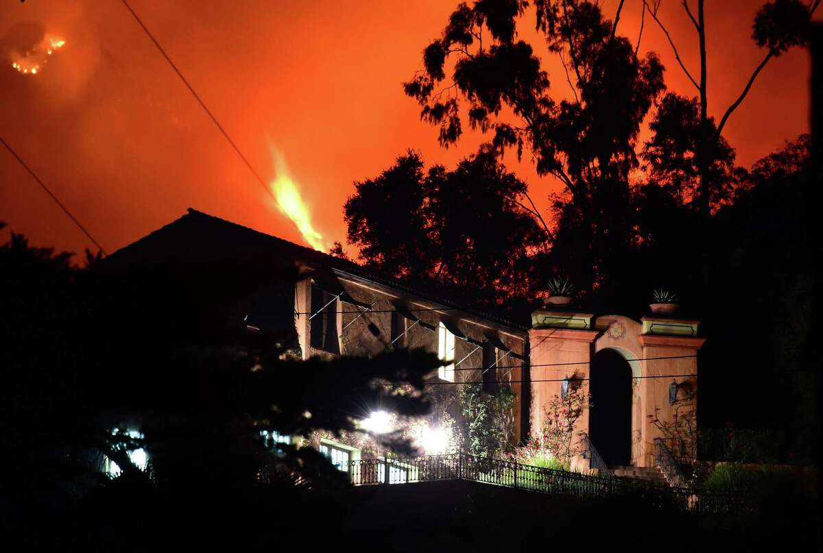 Flames from the Thomas Fire burn in the hills above homes in Montecito, California, east of Santa Barbara, December 11, 2017. It's been a week since southern California has been charred by a devastating wave of wildfires, blasted by almost hurricane force winds. Vast areas have been destroyed, hundreds of thousands of people have been evacuated and thousands of firefighters are working around the clock. The biggest concern is Thomas, which broke out last Monday and has already destroyed an area five times larger than the US capital Washington and threatens Pacific coast towns like Carpinteria, Summerland and Montecito. / AFP PHOTO / Robyn BeckROBYN BECK/AFP/Getty Images