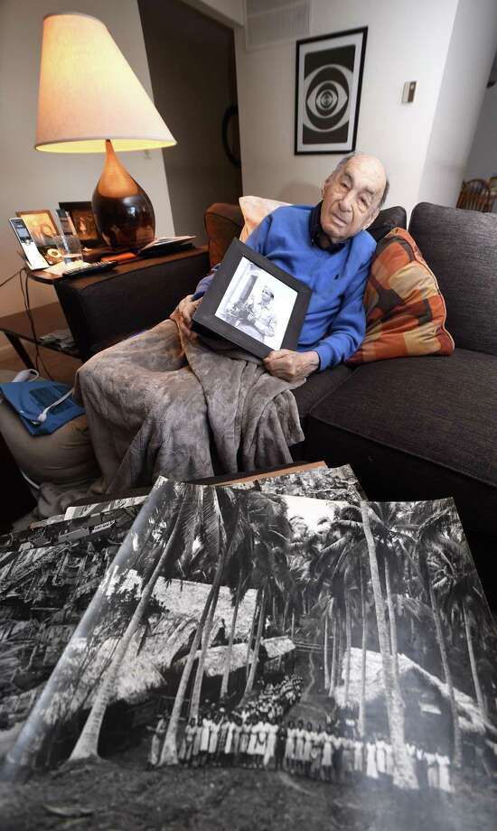 Ira Lewis holds a photograph of himself from his days as a photographer for the U.S. Army Signal Corps during World War II at his home in Branford. In the foreground is a photograph he took of a field hospital in the Philippines. Photo: Arnold Gold / Hearst Connecticut Media / New Haven Register