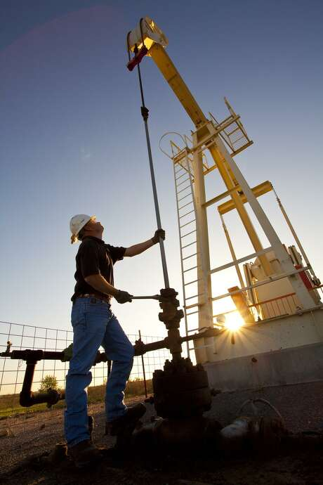 A pumpjack looms over a worker at a Linn Energy site in the Permian Basin of West Texas. Photo: Linn Energy / Linn Energy / Â2010 Ken Childress Photography