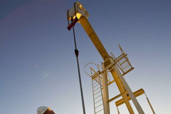 A pumpjack looms over a worker at a Linn Energy site in the Permian Basin of West Texas.
