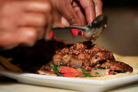 Tamearra Dyson, owner Souley Vegan, layers�Smart Ground�and other ingredients�on dough as prepares her vegan reinterpretation of the classic beef�Wellington�at Souly Vegan on Tuesday, November 21, 2017 in Oakland, Calif.