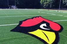 "The Greenwich High School Cardinal logo can be seen in the center of the field as workers from the Sprinturf Company headquartered in Atlanta, Ga., install the end zone lettering for the new artificial turf field at the high school's Cardinal Stadium, Conn., Wednesday afternoon, Aug. 24, 2016. Tim Karca, who was supervising and who was one of six workers who have been installing the field for the past three weeks said, "" We should be finished in a couple of days. It should be ready to be opened next Wednesday.""  Karca when asked what makes this turf field special responded ""The infill for the field is environmentally safe. It is also cooler because the sand coated plastic reflects heats."""