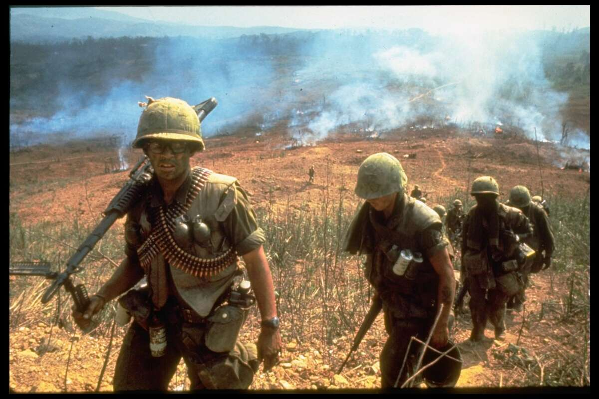 A line of American soldiers march up a hill during the Route 9 offensive while fires behind them send smoke into the air, Vietnam, 1968.