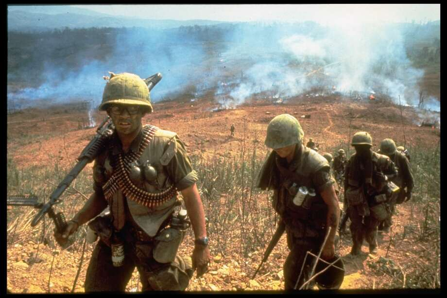 A line of American soldiers march up a hill during the Route 9 offensive while fires behind them send smoke into the air, Vietnam, 1968. Photo: Larry Burrows/The LIFE Picture Collection/Gett