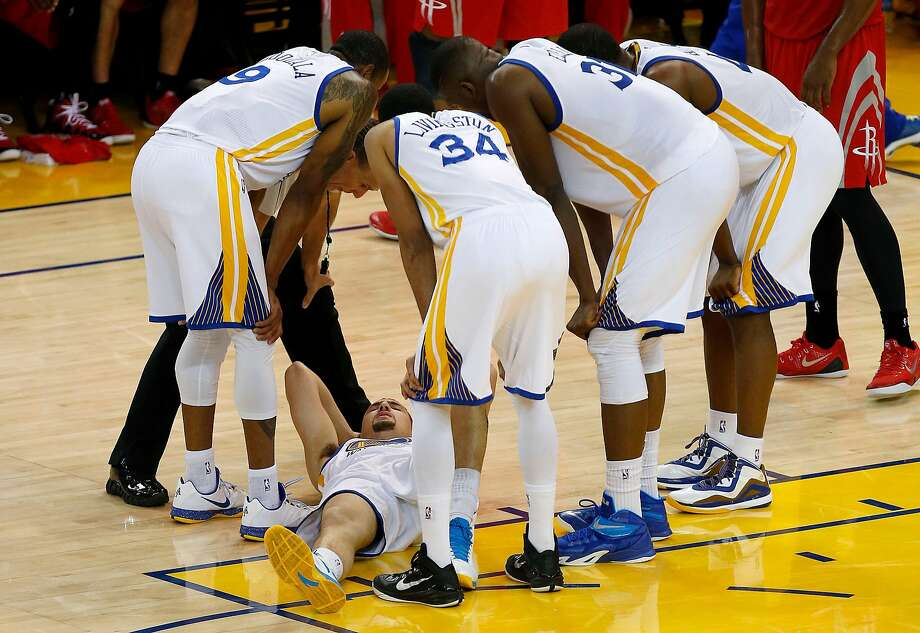 In this photo taken May 27, 2015, Golden State Warriors guard Klay Thompson, bottom, is checked on by teammates after taking a knee to his head from Houston Rockets forward Trevor Ariza during the second half of Game 5 of the NBA basketball Western Conference finals. The Warriors hope to get healthy and stay in tune over the next week before facing the Cleveland Cavaliers in the NBA Finals. Thompson needs to pass through the league's concussion protocol and Stepehen Curry is trying to get his aching body back at full strength.  (AP Photo/Tony Avelar, File Photo: Tony Avelar, Associated Press