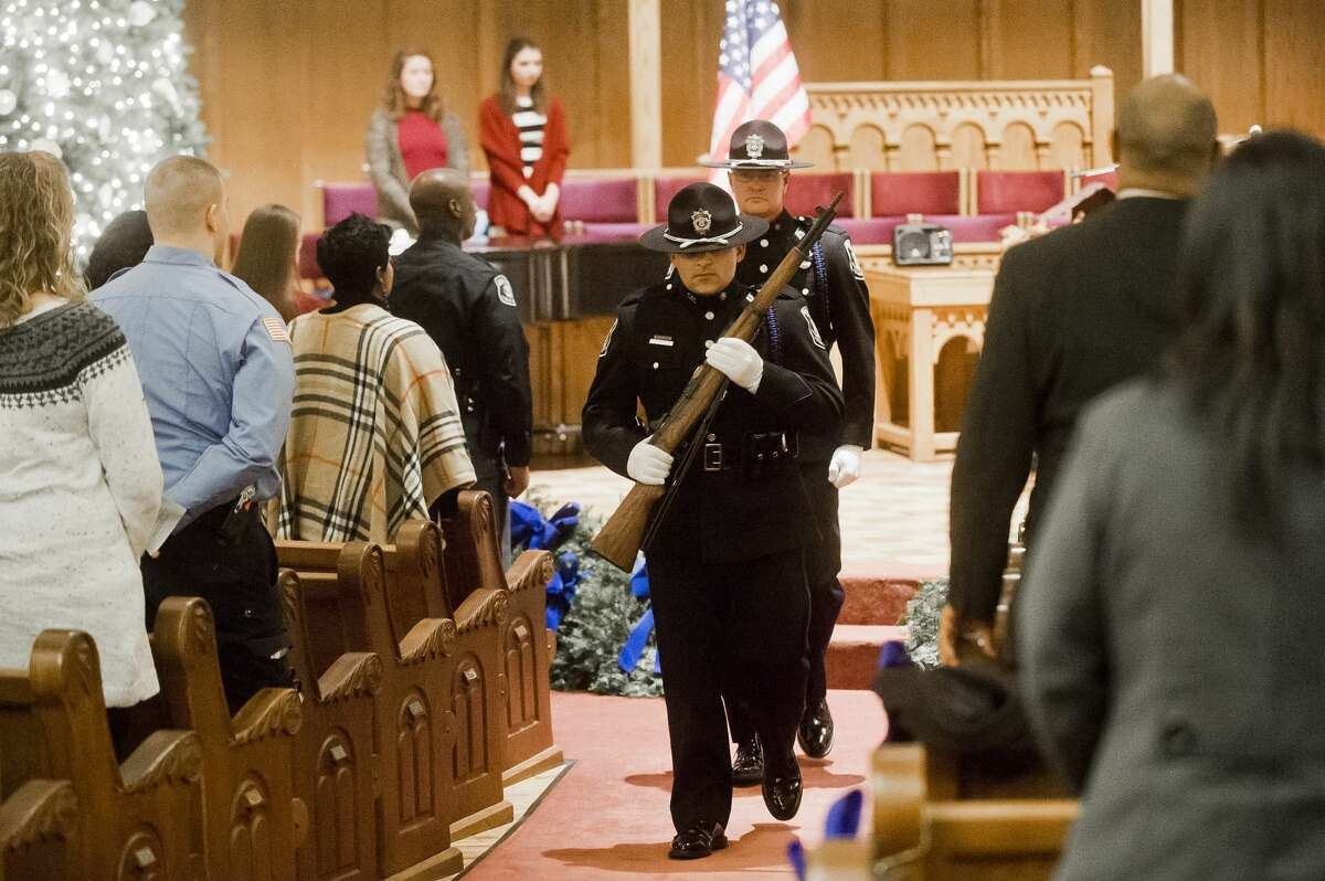 Officer Eddie Hinson, front, and Officer Scott Coyle, back, both of the Midland Police Honor Guard, march through the church after the presentation of colors during the Project Blue Light ceremony on Wednesday, Dec. 13, 2017 at First Presbyterian Church in Bay City. (Katy Kildee/kkildee@mdn.net)