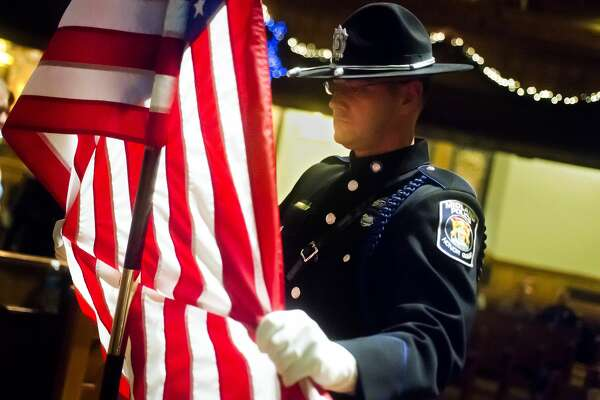 Officer Scott Coyle of the Midland Police Honor Guard spreads the American flag as the group does a run-through of the presentation of colors before participating in the Project Blue Light ceremony on Wednesday, Dec. 13, 2017 at First Presbyterian Church in Bay City. (Katy Kildee/kkildee@mdn.net)