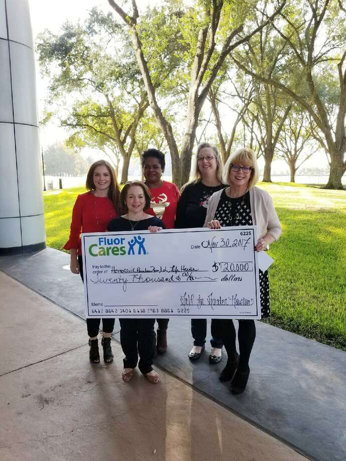 Front, from left, are Tracy Mooney from Fluor and Bette Moser, HomeAid Houston; from left, second row, are April Nemec, Barbara Jones and Rebecca Schoenherr from Fluor, presenting the check.