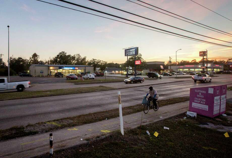 A man rides a bike past a pawn shop, located near the intersection of Homestead Road and Tidwell Road, Friday, Dec. 1, 2017, in Houston. The pawn shop was looted during Hurricane Harvey, and dozens of firearms were stolen.  ( Jon Shapley / Houston Chronicle ) Photo: Jon Shapley, Houston Chronicle / © 2017 Houston Chronicle