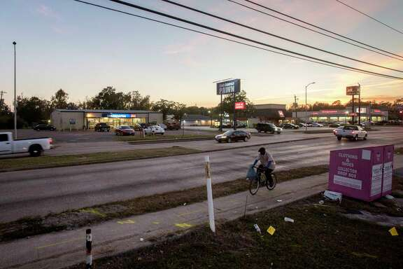 A man rides a bike past a pawn shop, located near the intersection of Homestead Road and Tidwell Road, Friday, Dec. 1, 2017, in Houston. The pawn shop was looted during Hurricane Harvey, and dozens of firearms were stolen.  ( Jon Shapley / Houston Chronicle )