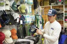Jason Coleman with his Salty Sea Tee shirts and hats that are sold at tackle shop Fisherman's World in East Norwalk, Conn., pictured on Friday, Dec. 15, 2017.