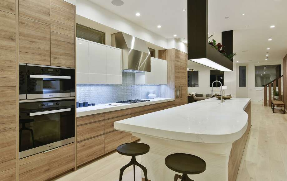 The kitchen features a 10-foot island, an integrated cooktop, and glass tile backsplash. / ONLINE_CHECK