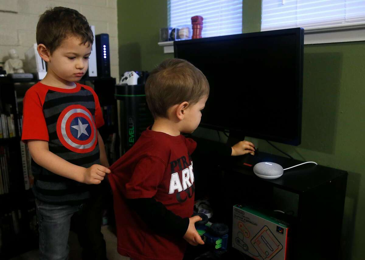 Colin Martin, 5, and his brother Bradley, 2, talk to their Google Home Mini smart speaker in Concord, Calif. on Friday, Dec. 8, 2017.