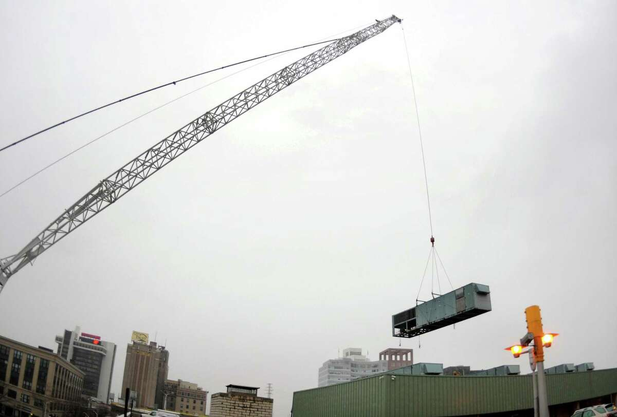 Crews from Bay Crane Service of Connecticut and A&A Crane and Rigging in Bridgeport, work to remove several HVAC (heating, ventilation and air conditioning) units from the roof of the Margaret E. Morton Government Center. on John Street in Bridgeport, Conn., on Friday Dec. 15, 2017. John Street will remain closed between Broad Street and Lafayette Street until 9 a.m. Monday Dec. 18th.