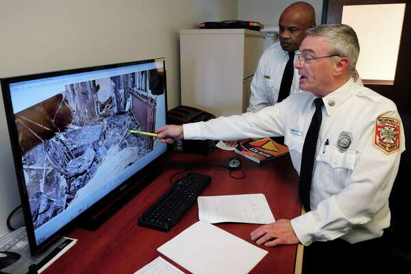 Norwalk Fire Marshal Broderick Sawyer and Deputy Fire Marshal Kirk McDonald point out methods of detecting the source of the fire at StoneWood Condominium on Richards Avenue while at the Norwalk Fire Department Headquarters on Connecticut Avenue Thursday.