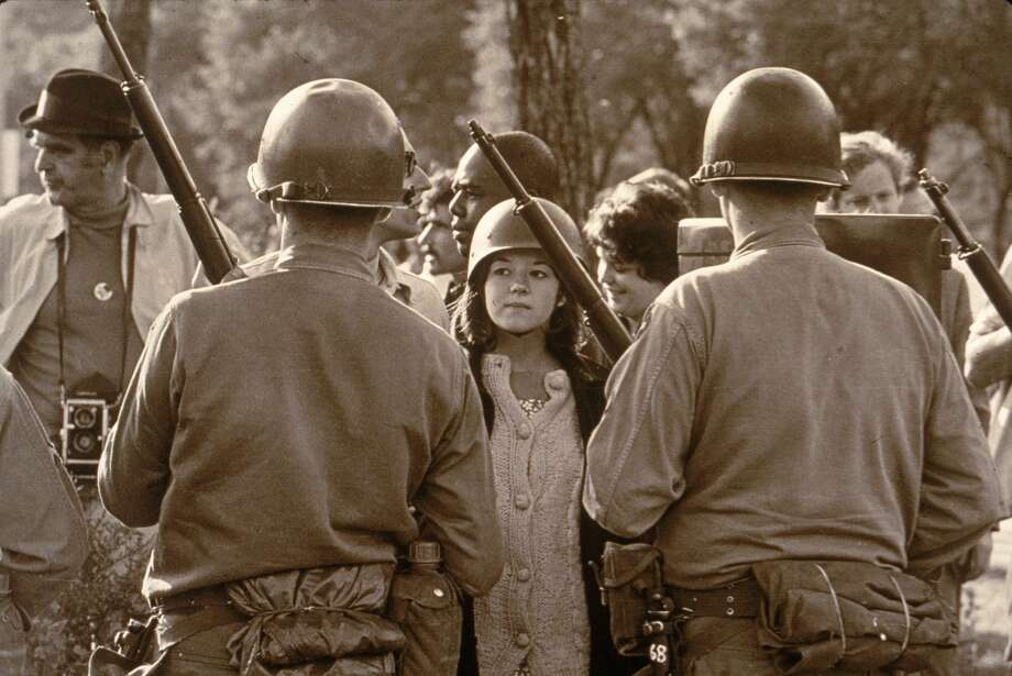 A young female protester wearing a helmet faces down helmeted and armed police officers at an anti-Vietnam War demonstration outside the 1968 Democratic National Convention, Chicago, Illinois, August 1968. Photo: Hulton Archive/Getty Images