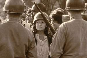 A young female protester wearing a helmet faces down helmeted and armed police officers at an anti-Vietnam War demonstration outside the 1968 Democratic National Convention, Chicago, Illinois, August 1968.