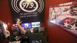 "KCJV radio owner Chris Varelas re-creates one of his favorite DJ scenes from ""American Graffiti"" in his home broadcast studio. KCJV is a low-power radio station that plays rarely heard oldies, many from long-forgotten San Antonio groups."