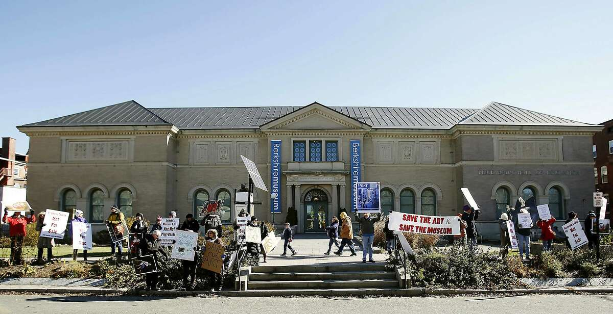 FILE - In this Nov. 11, 2017 file photo, some 30 protesters gather outside of the Berkshire Museum in Pittsfield, Mass., holding signs bearing pleas to
