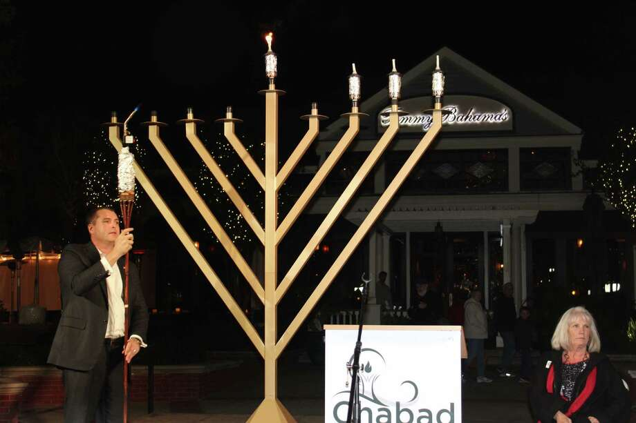Gordy Bunch lights the shamash candle, or candle of service, during the menorah lighting ceremony at The Grand Chanukah Celebration at Market Street on Dec. 14. Photo: Patricia Dillon