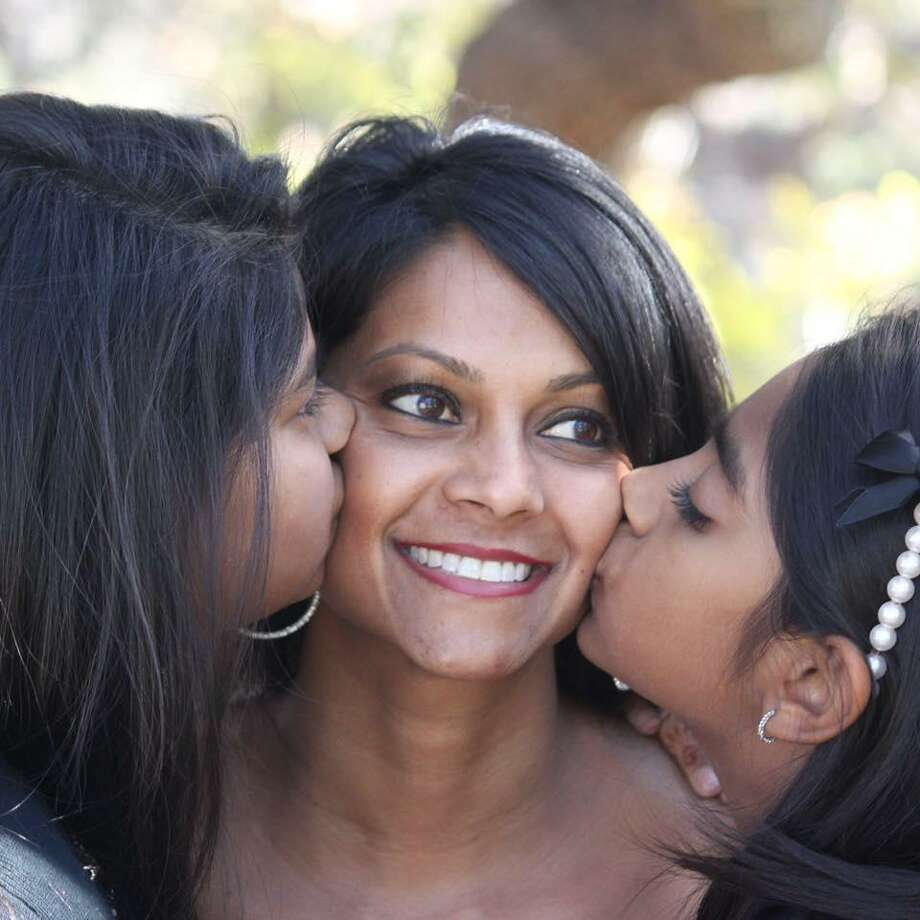 A San Antonio single mom and CNN Hero Mona Patel gets appreciative kisses from her two daughters before embarking on a special trip to New York where she'll be honored on a national TV special Sunday night. Photo: Courtesy Mona Patel