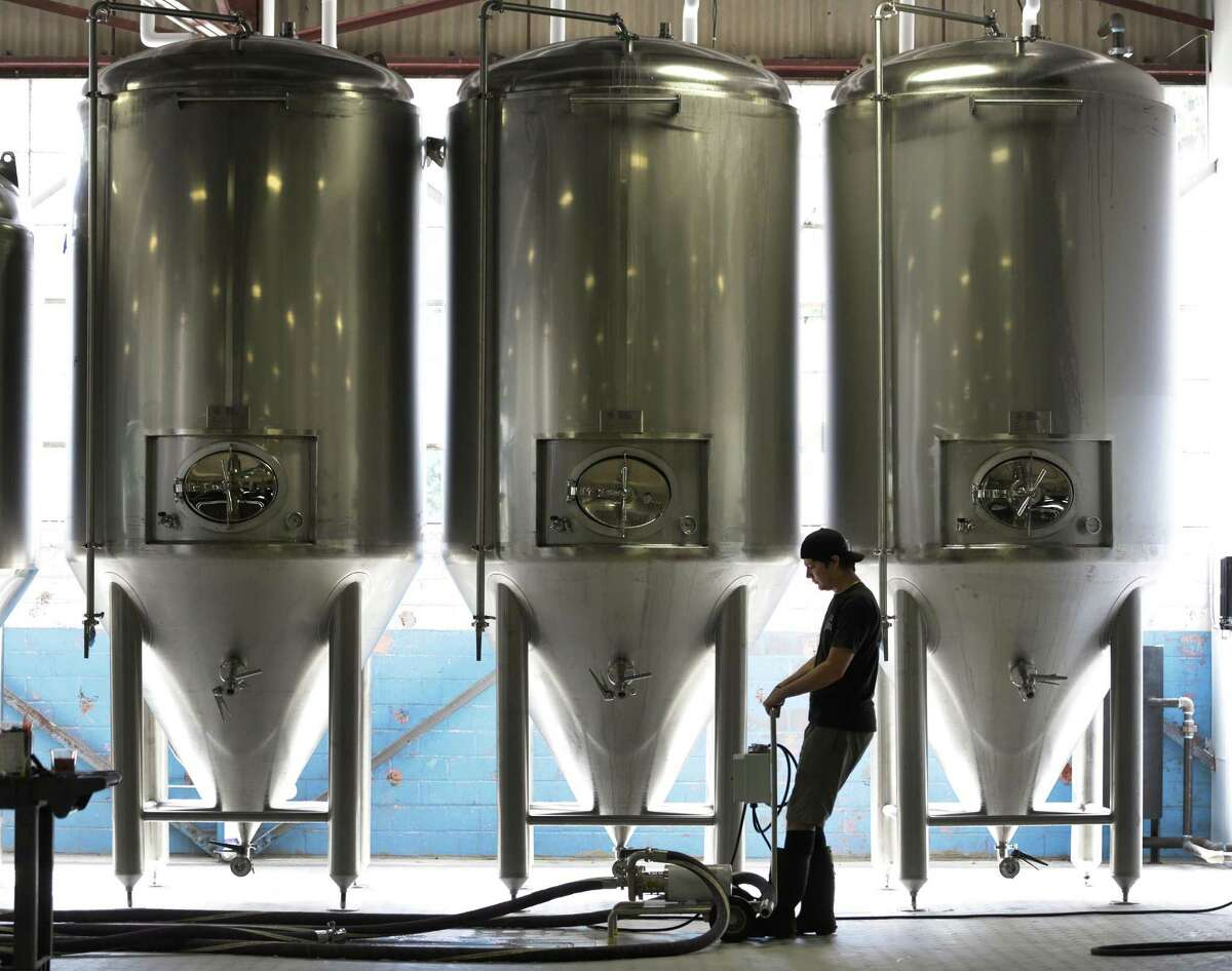 An employee at Freetail Beer prepares to sanitize fermintation tanks at the company's South Presa. The craft brewer has received buyout offers but refused.