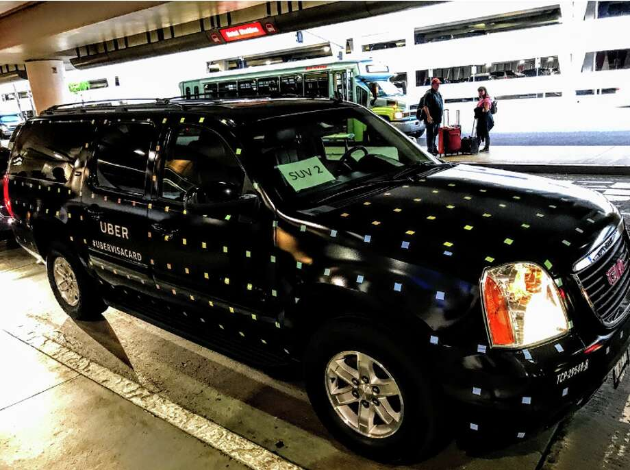 SFO is moving some high-end Uber rides back to the curbside in a test. Pictured: a specially wrapped Uber Black SUV Photo: Chris McGinnis