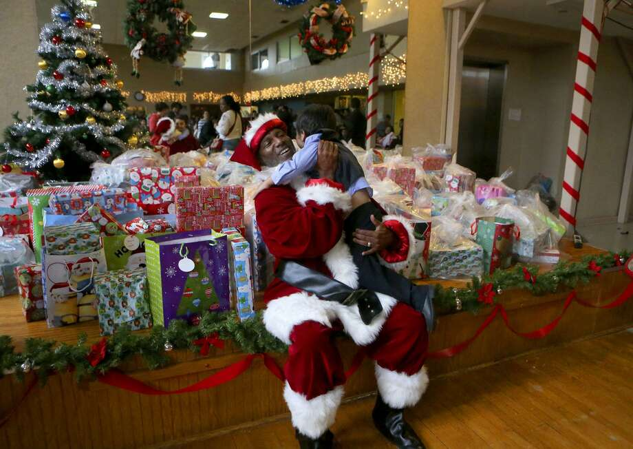 Santa Claus greets Mikel (cq) Cruchelow,4, Friday December 15, 2017 at a Christmas party held at Our Lady of the Lake University for the children of participants of Bexar County's Family Drug Court and Early Intervention Program. About 150 kids were treated to pizza and Christmas gifts at the event. Cruchelow was there with his father Mikel Cruchelow (same name) and his mother Linda Guzman and his sister Xena Cruchelow,3. Photo: John Davenport, STAFF / San Antonio Express-News / ©John Davenport/San Antonio Express-News