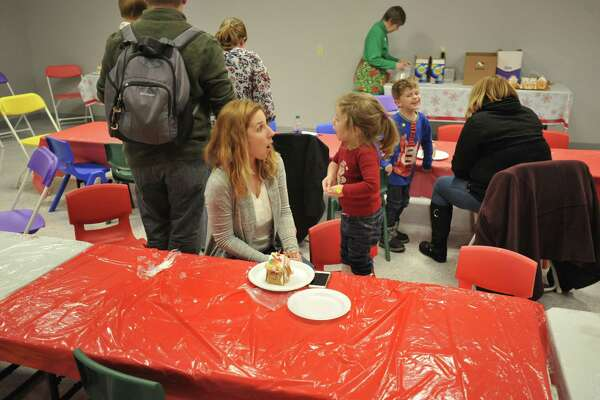 As the snow fell Friday evening in Torrington, families came together to make gingerbread houses at the KidsPlay Childrens Museum. Above, Stephanie and Emerson Michaud.