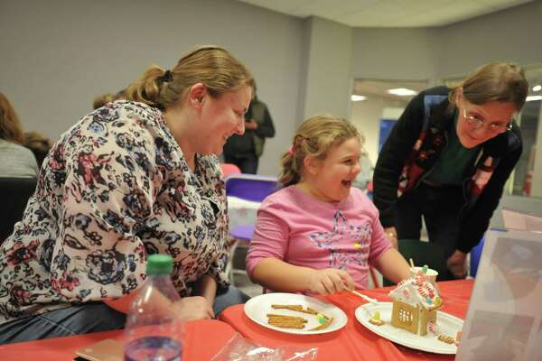 As the snow fell Friday evening in Torrington, families came together to make gingerbread houses at the KidsPlay Childrens Museum. Above, Izabela Nizinski and Thora Holmgren.