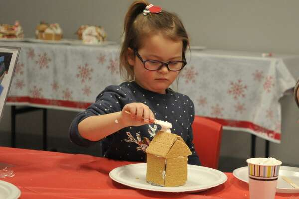 As the snow fell Friday evening in Torrington, families came together to make gingerbread houses at the KidsPlay Childrens Museum. Above, Elina Karouta.
