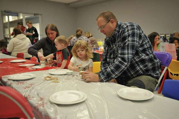 As the snow fell Friday evening in Torrington, families came together to make gingerbread houses at the KidsPlay Children's Museum.