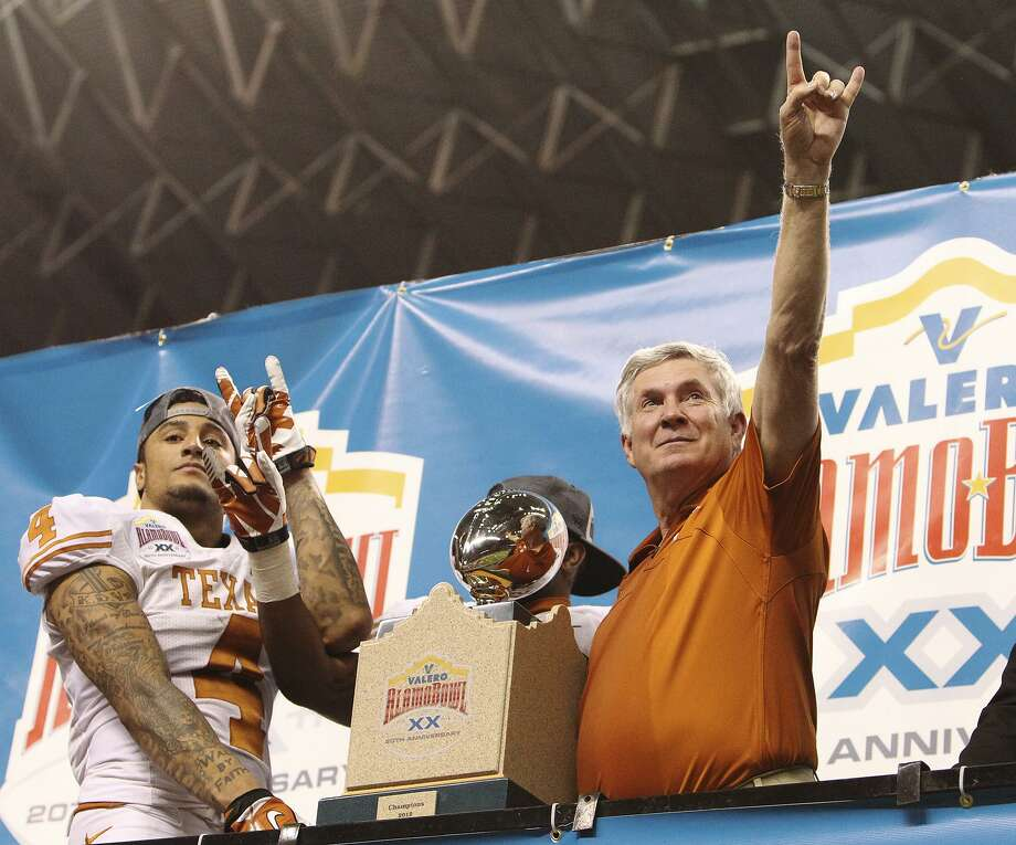 Texas head coach Mack Brown shows the Longhorn sign along with player Kenny Vaccaro (04) after receiving the 20th Valero Alamo Bowl trophy for defeating Oregon State on Dec. 29, 2012. Texas won, 31-27. Photo: Kin Man Hui /San Antonio Express-News / © 2012 San Antonio Express-News