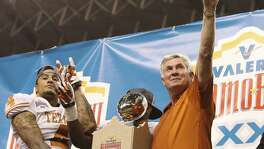 Texas head coach Mack Brown shows the Longhorn sign along with player Kenny Vaccaro (04) after receiving the 20th Valero Alamo Bowl trophy for defeating Oregon State on Dec. 29, 2012. Texas won, 31-27.