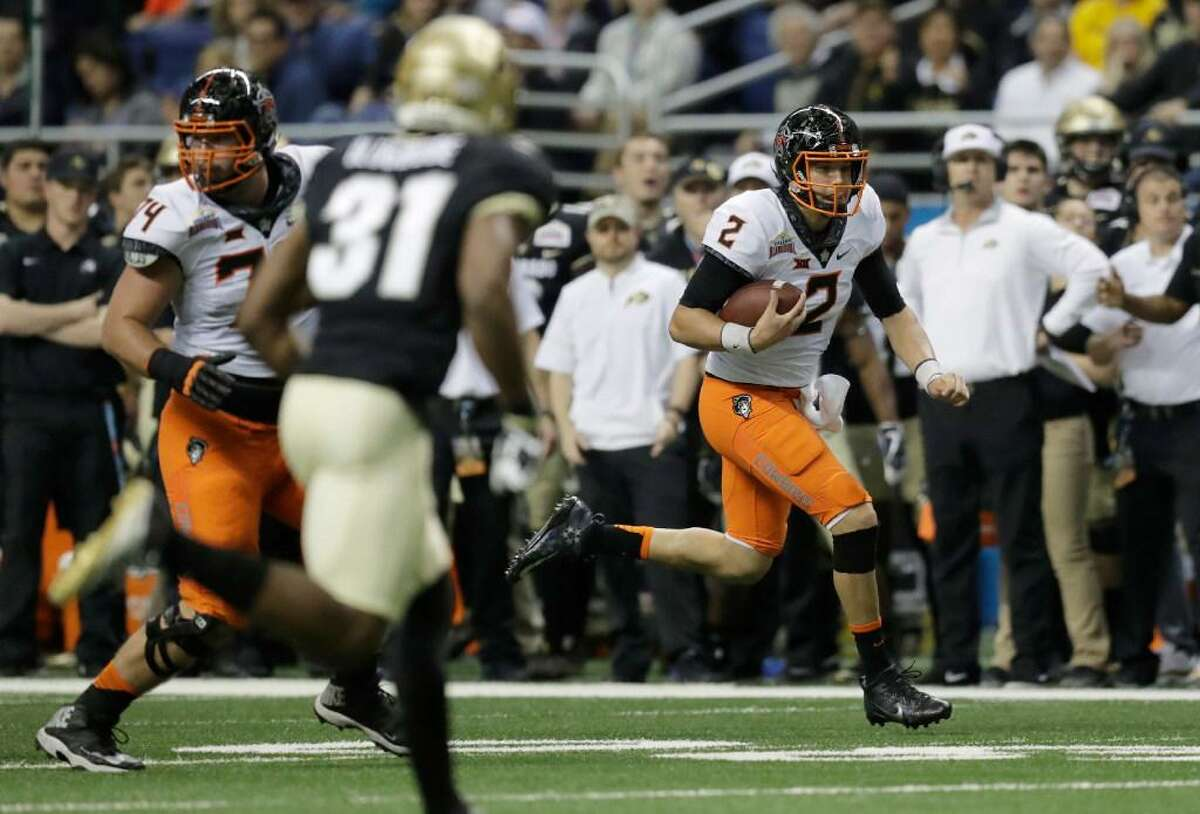 Oklahoma State quarterback Mason Rudolph (2) runs up field against Colorado after making a catch during the first half of the 2016 Alamo Bowl. The Cowboys won 38-8.