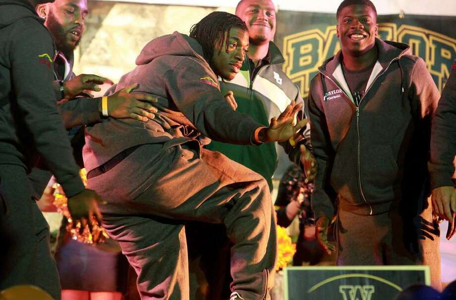 Baylor quarterback and Heisman Trophy winner Robert Griffin III remains frozen in the Heisman Trophy pose, which he struck for his teammates to carry him onstage during a pep rally on the Riverwalk in San Antonio on Dec. 27, 2011. Baylor beat Washington in the 2011 Alamo Bowl. Photo: Tom Reel /San Antonio Express-News